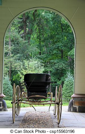 Stock Photographs of Arched entry with old horse buggy.