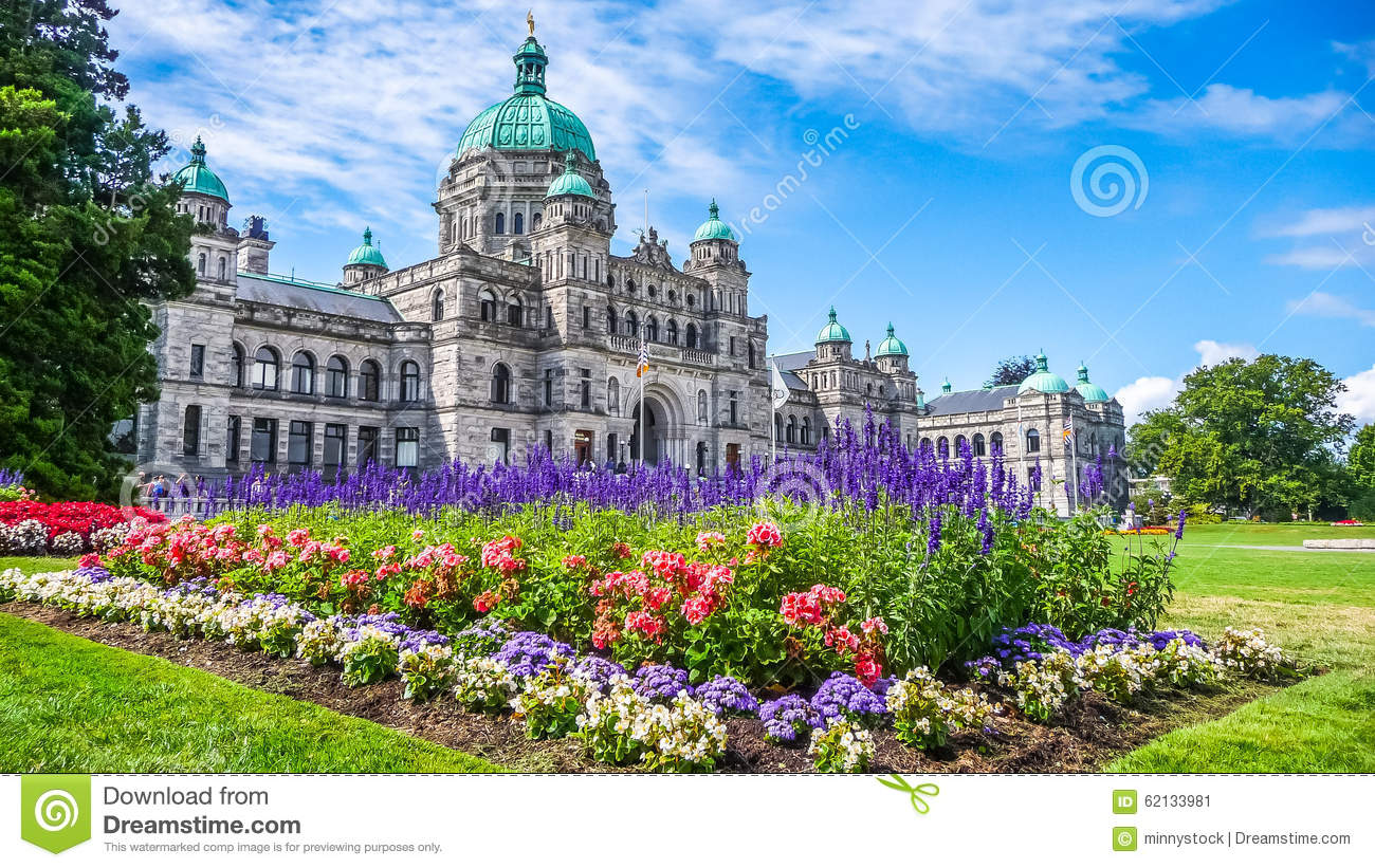 Historic Parliament Building In Victoria With Colorful Flowers.