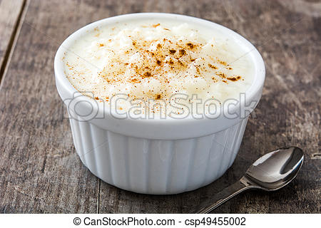 Arroz con leche. Rice pudding with cinnamon on wooden background.