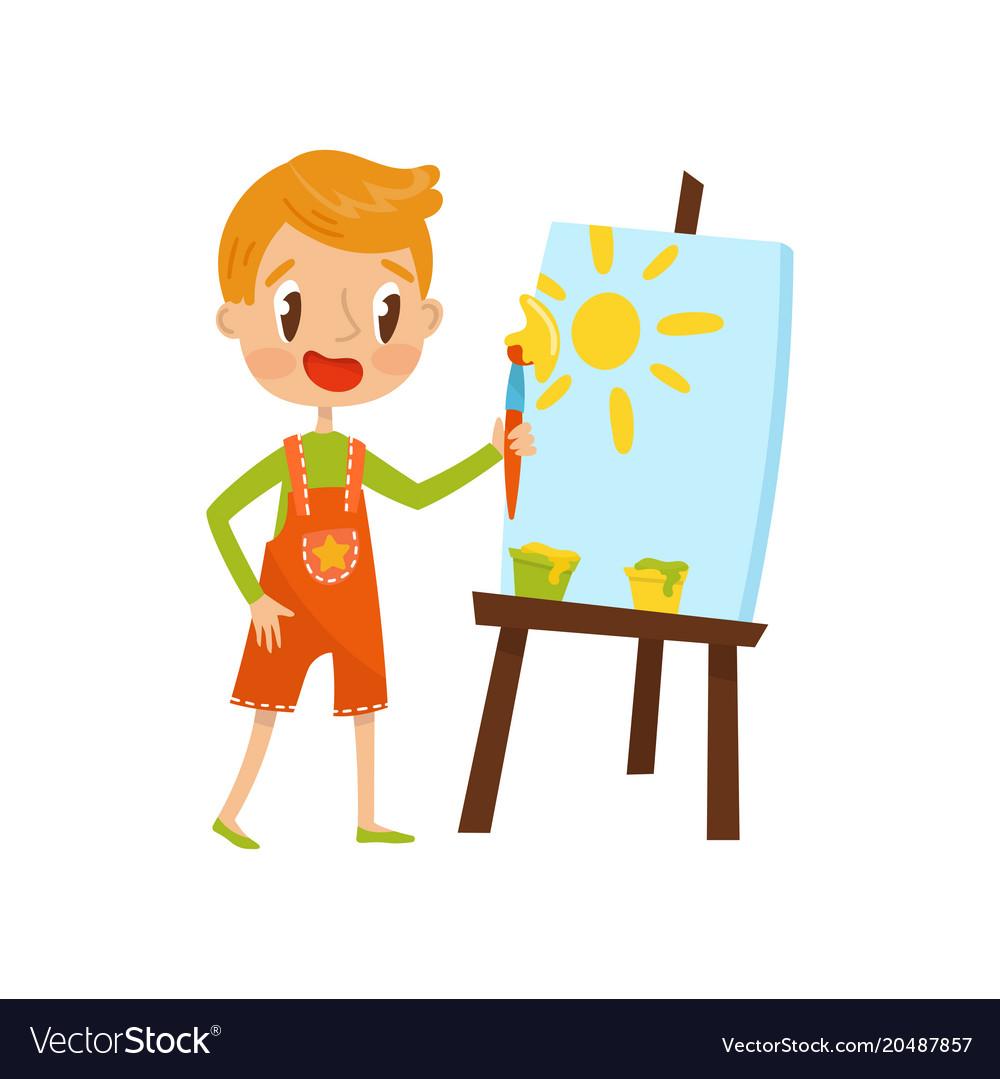 Cute little boy painting sun on an easel kids.