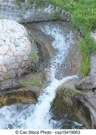 Stock Images of An artificial brook in the park with grass.