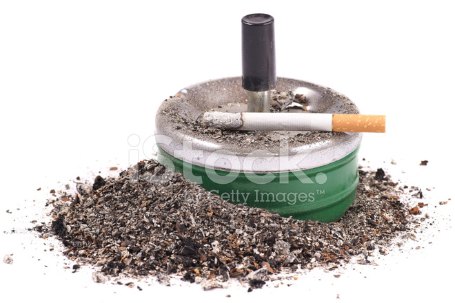 Lighted Cigarette With A Filter on The Ashtray and Ashes.