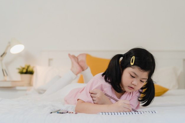 Young asian girl drawing at home. asia japanese woman child.