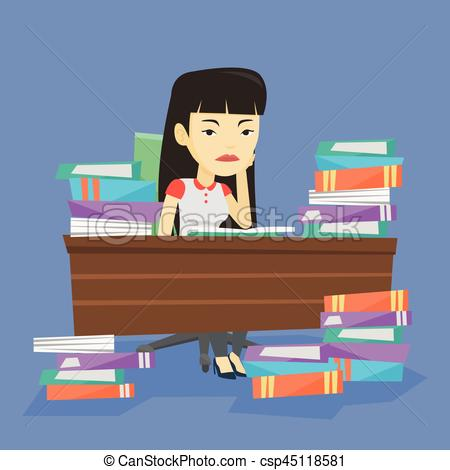 Student sitting at the table with piles of books..