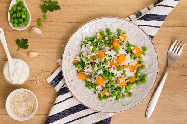 Riz aux haricots verts et carottes sur assiette près de.