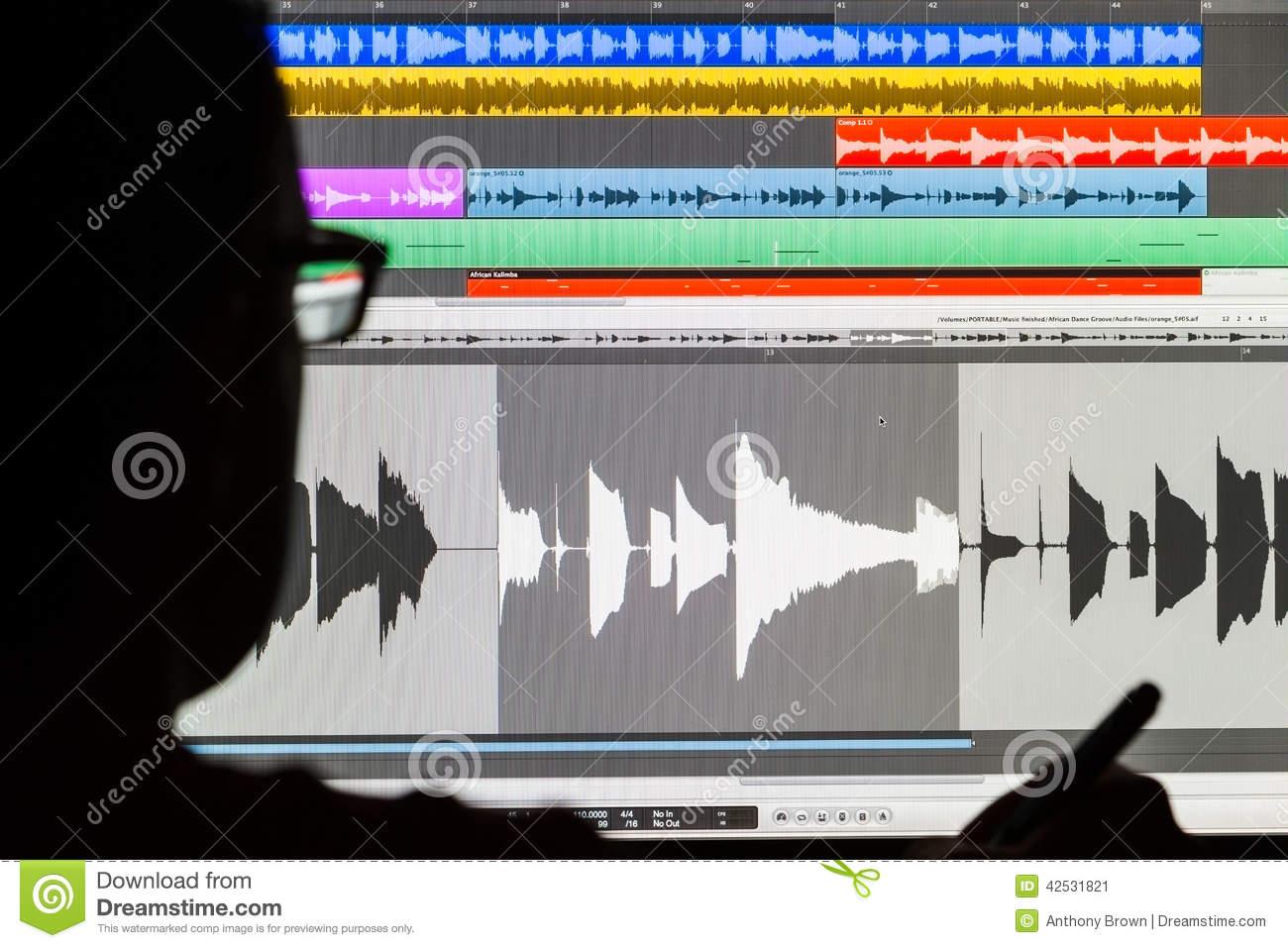 Man Editing Digital Audio On A Computer Stock Photo.