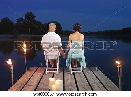 Picture of Germany, Augsburg, Couple sitting on dock at dusk.