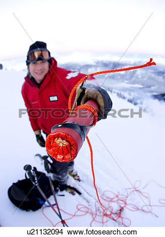 Stock Photo of Man with explosives carrying out avalanche control.