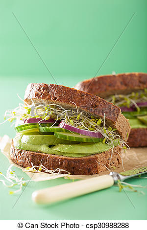healthy avocado sandwich with cucumber alfalfa sprouts onion.