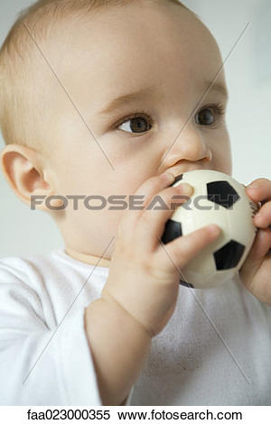 Stock Image of Baby putting toy soccer ball in mouth, close.