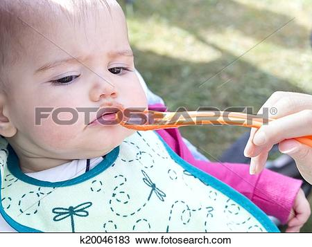 Stock Photo of baby girl doesn't open his mouth to eat food.