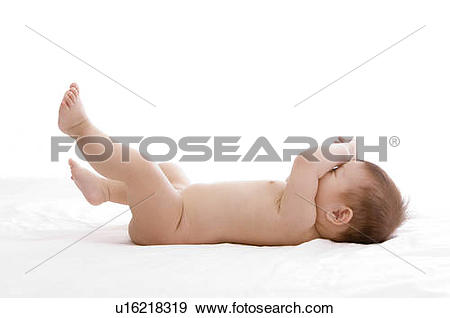 Stock Photograph of Baby boy lying on his back, covering eyes with.