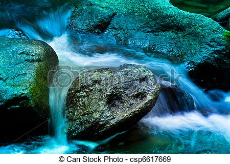 Stock Photographs of Bach in the water with stones and mountains.