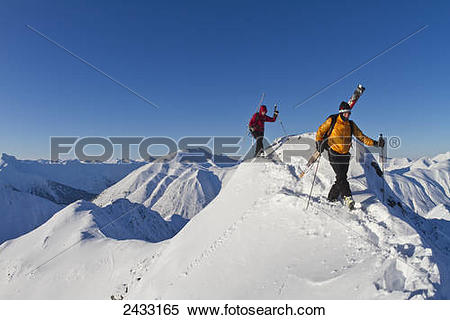 Stock Image of Couple climbing a snow ridge for back country.
