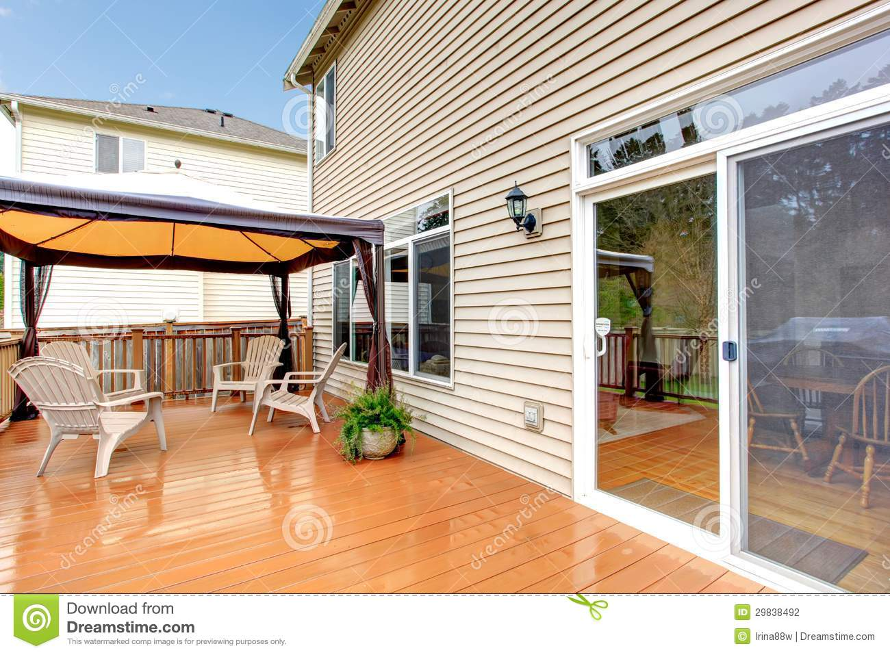 House Back Porch With Umbrella And Chairs During Rain. Stock.