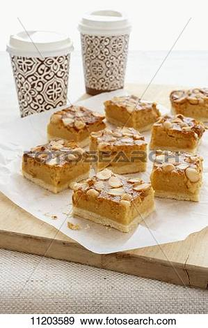 Stock Photograph of Macadamia nut slices with coffee in takeaway.