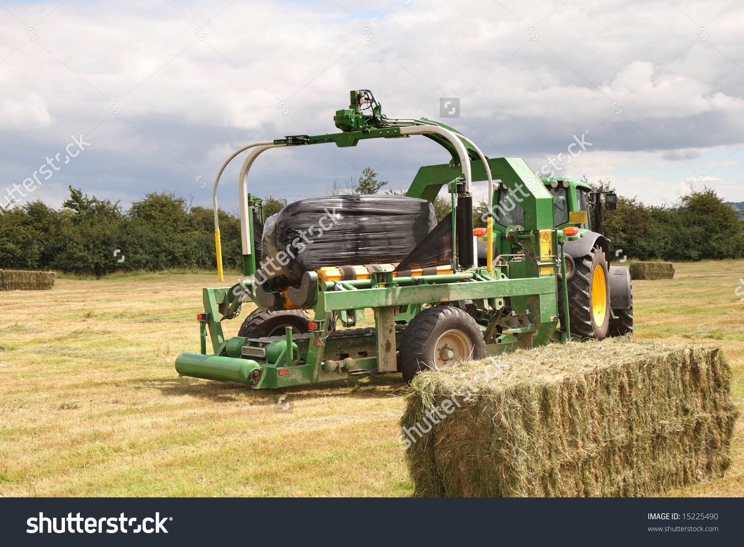 Tractor And Baling Machine Baling Hay In A Rural English Field.