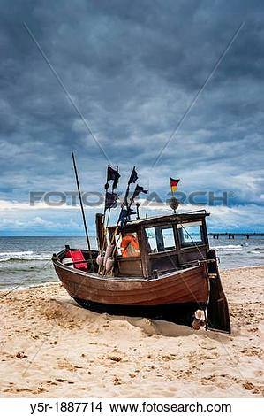 Stock Photo of Fishing boat at the Baltic Sea near the pier of the.