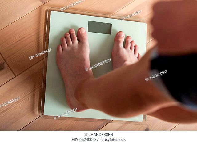 Overweight boy on scales Stock Photos and Images.