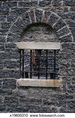 Stock Photography of Barred window in arched stone window.