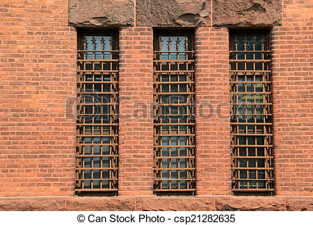 Stock Photos of Three long barred windows in brick.