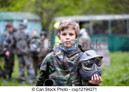 Picture of Boy in the camouflage holds a paintball gun barrel up.