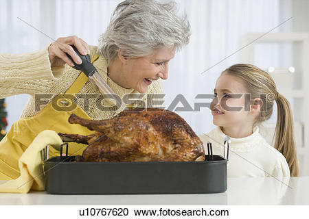 Stock Photography of Grandmother and daughter basting roast turkey.