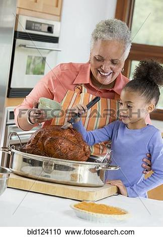 Stock Photography of Black woman and granddaughter basting turkey.