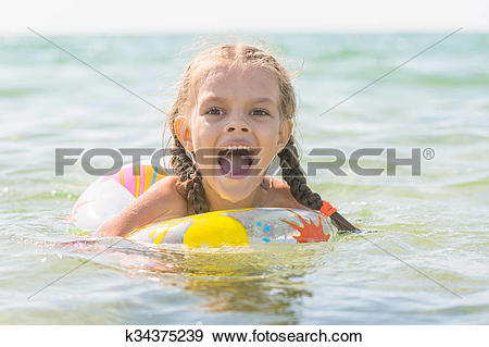 Stock Photograph of Six year old girl bathing in the sea with his.