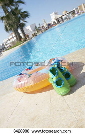Pictures of Bathing shoes and inflatable ring by pool side.