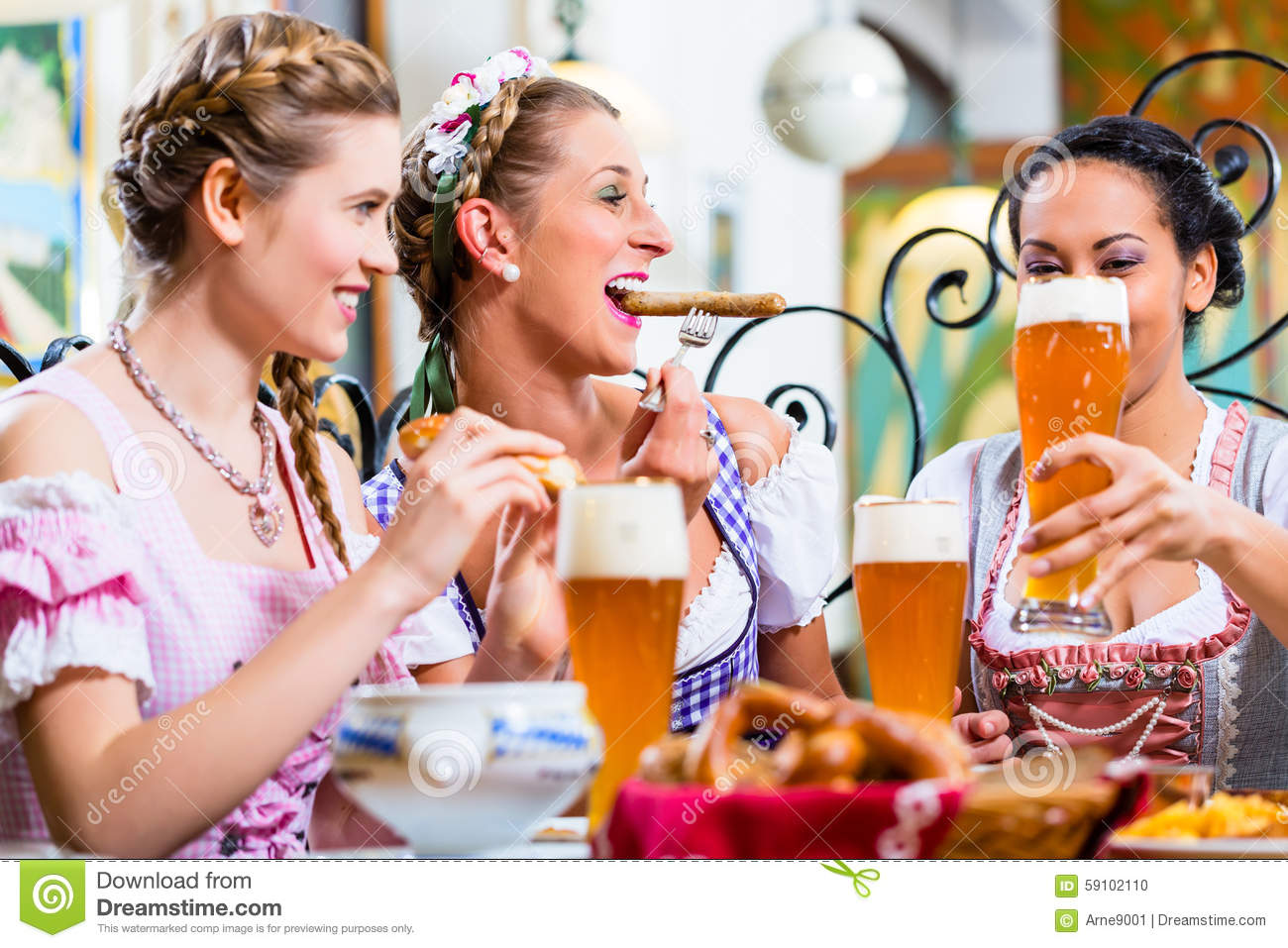 Women In Bavarian Pub Eating Food For Dinner Stock Photo.