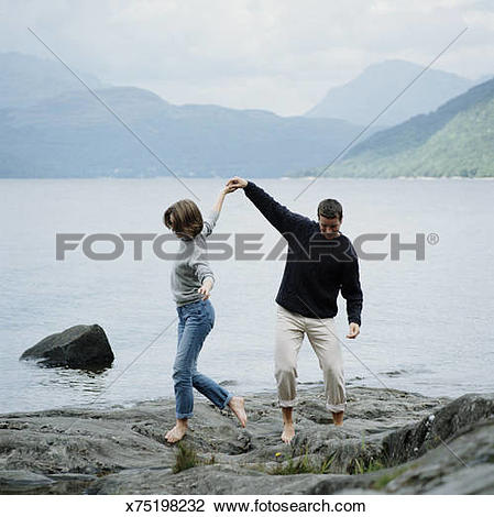 Stock Photo of Couple walking bare foot hand in hand over beach.