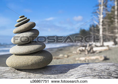 Stock Photography of A pile of balancing smooth beach rocks near.