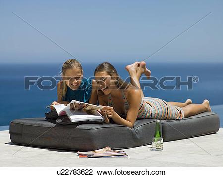Stock Photo of Women lying down and reading magazines. u22783622.