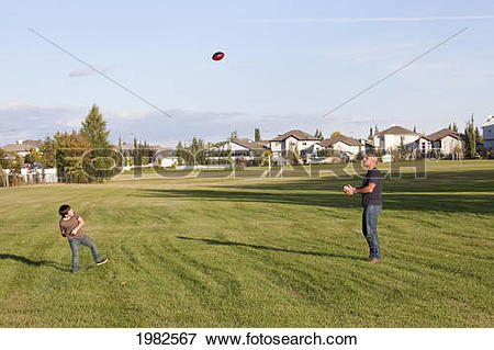 Picture of father and son playing football in a park; beaumont.