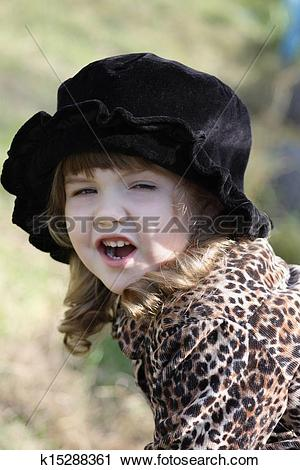 Stock Photography of Beautiful little girl in black hat shouts.