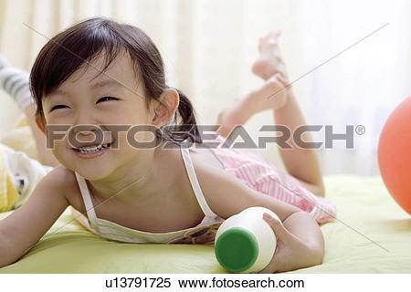 Stock Image of Girl holding milk bottle in bed u13791725.