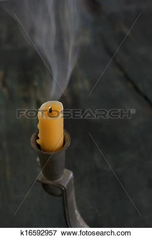 Picture of A Smoking Beeswax Candle in an Old Pewter Holder.