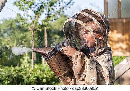 Stock Images of Young beekeeper boy using a smoker on bee yard.