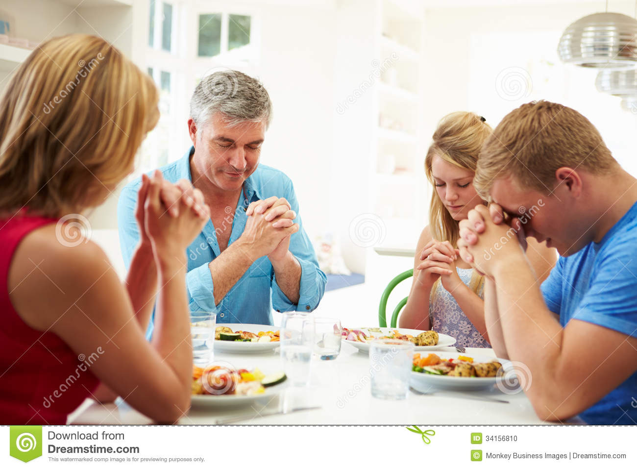 Family Saying Prayer Before Eating Meal At Home Together Stock.