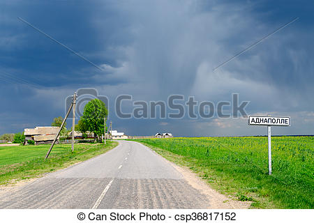 Stock Images of Country road with a signpost before rain.