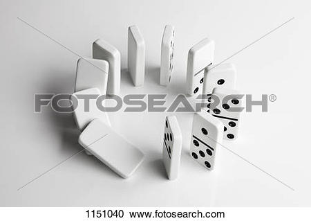 Stock Photography of Dominoes in a circle beginning to fall over.