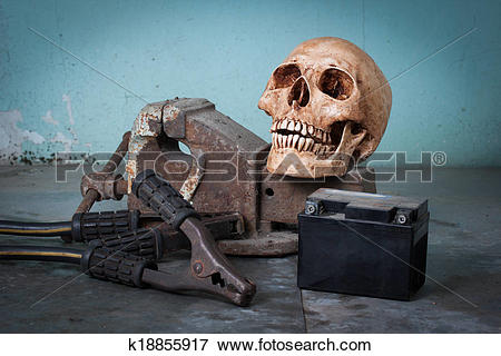 Picture of Group of objects on table. human skull, bench vise.