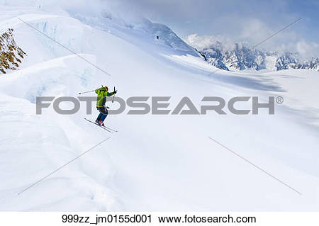 Stock Photography of Skier jumping a bergschrund crevasse onto.