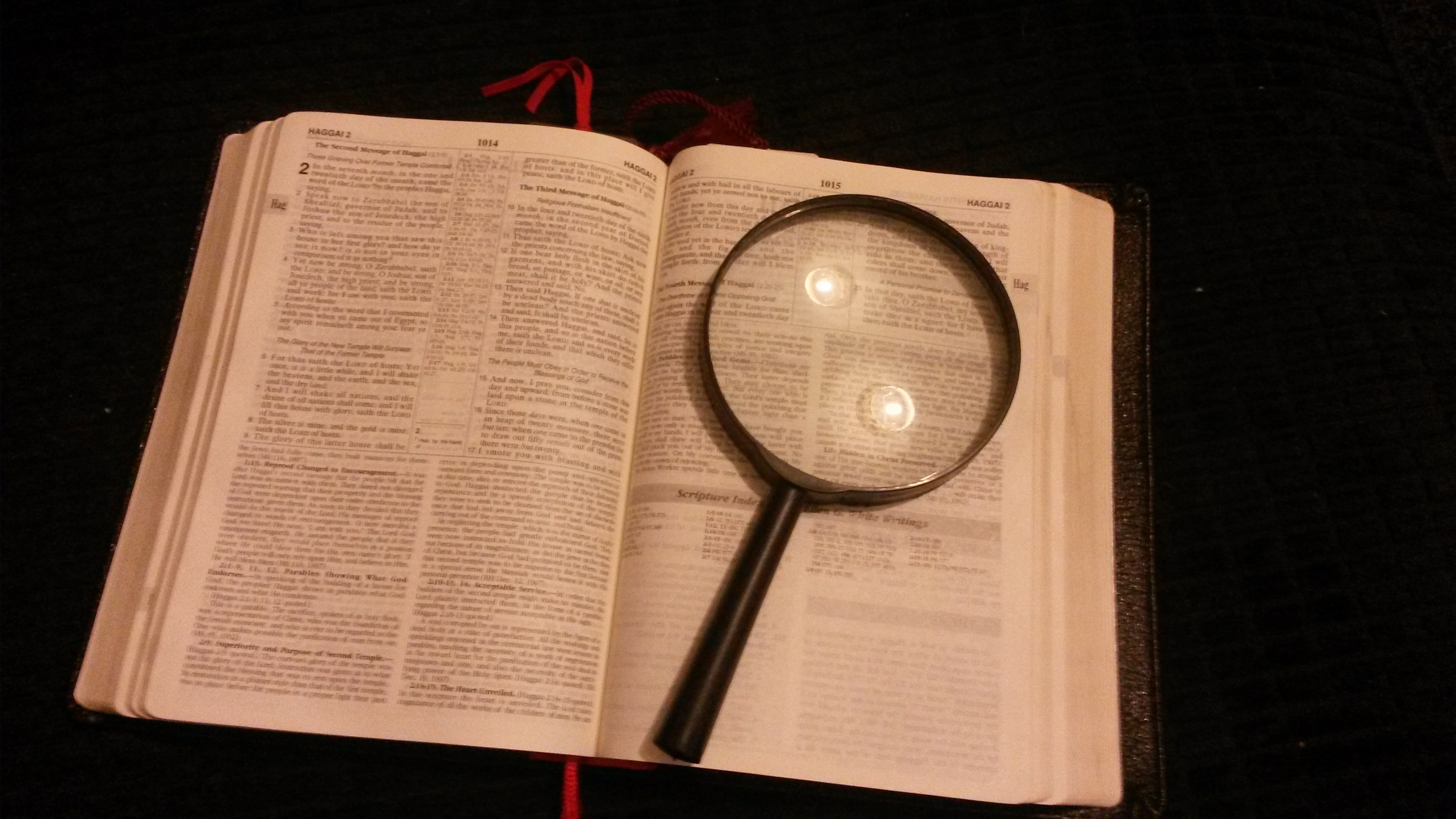 Opened bible and magnifying glass free image.