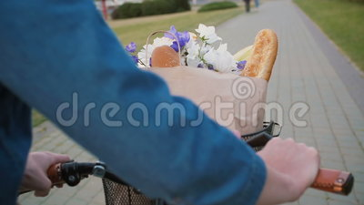 Woman Hands On Handlebar Of Bike With Flowers And Bread In Basket.