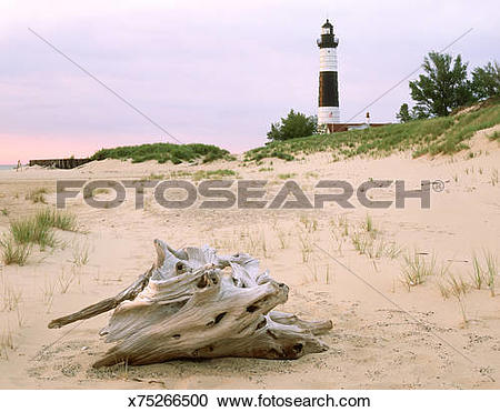 Stock Photography of sunset on big sable point lighthouse on shore.
