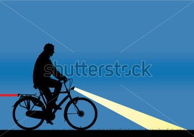作為剪影與後方和前的大燈上夜騎自行車的人。作為帶區的尾燈。 付費.