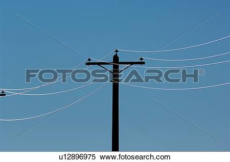 Stock Image of sun power pole electric cables backlit rising.