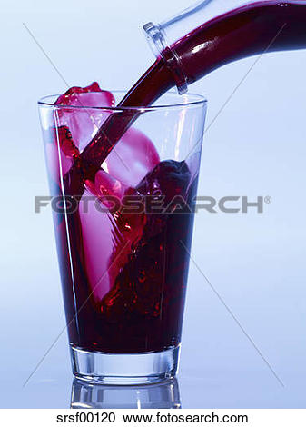 Stock Photography of Pouring black currant juice in glass, close.